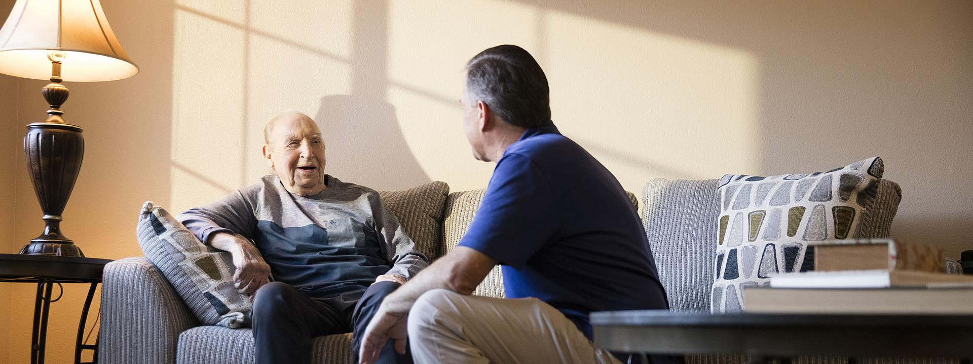 Caregiver and resident sitting a the couch smiling and talking
