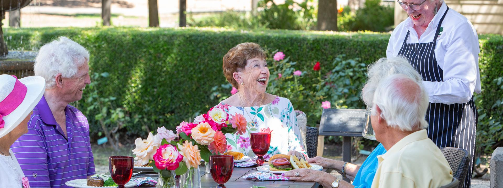 Residents laughing and enjoying lunch on the patio