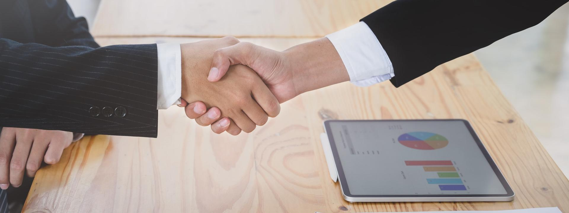 Hand shake with computer on the table