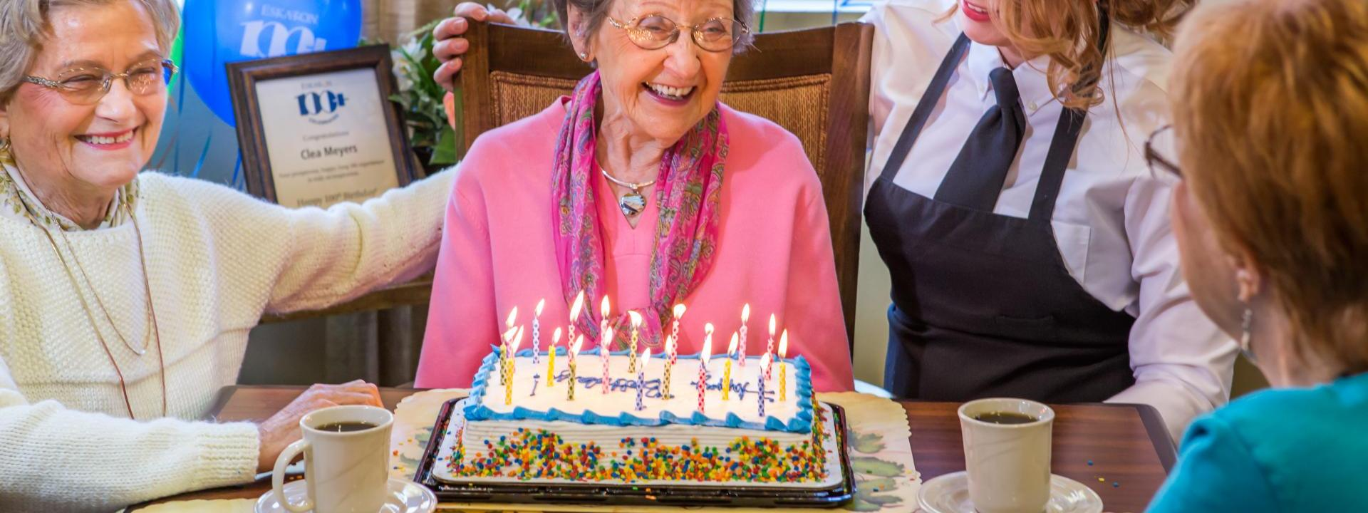woman celebrating her 100th birthday with friends