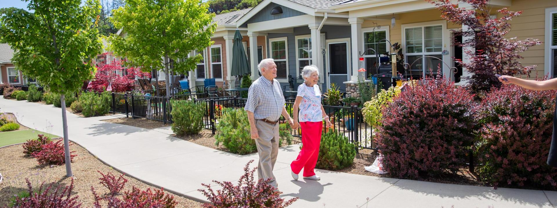 Resident couple walking holding hand and hand.