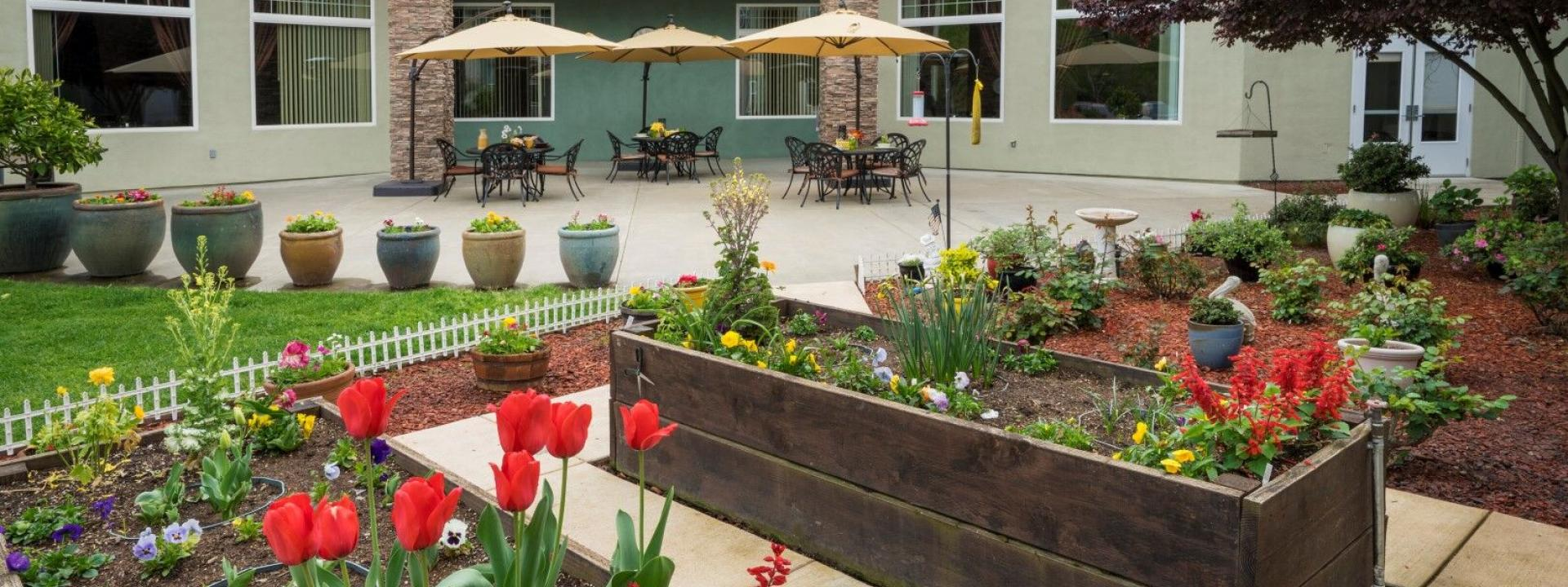 Outdoor patio with round table, chair, umbrellas, flower garden and potted plants