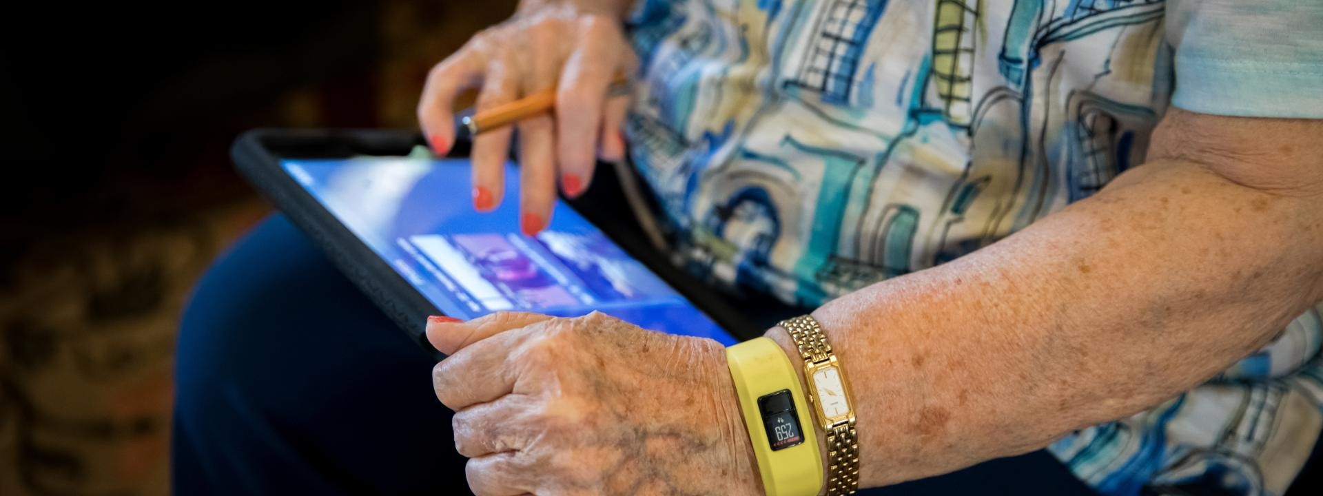 Resident using her iPad and wearing a smart watch.