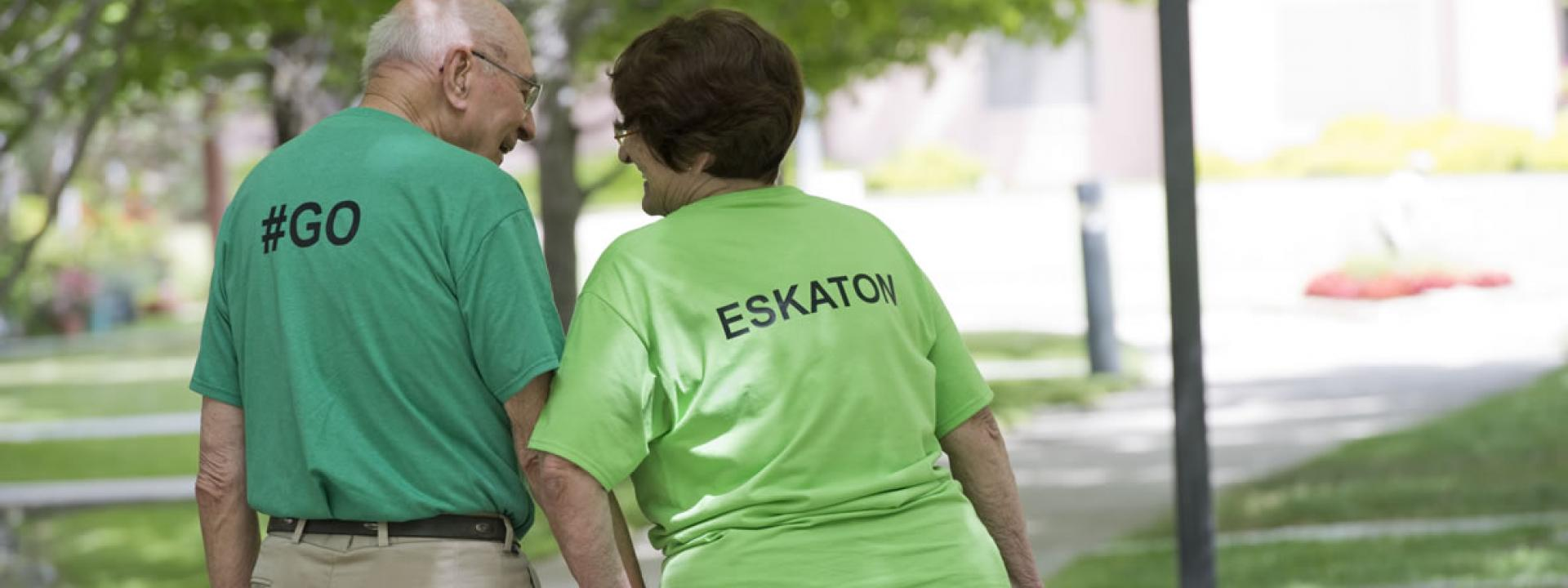 Residents taking a walk, holding hands and wearing Go Eskaton t-shirts