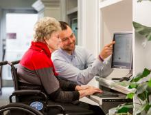 Staff teaching resident how to use the computer and some programs.