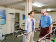 Male resident receiving walking therapy with staff assisting him.