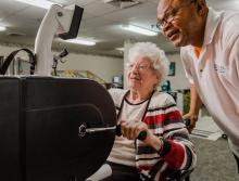 Woman resident on a stationary bike for therapy with staff standing next to her.