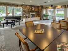 Community recreation room with piano and fireplace