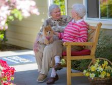 Two women sitting outside on a bench talking.