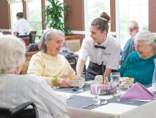 Three women smiling and talking to the waitress in the dining room.