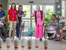 A woman resident bowling as staff and other residents cheer her on.