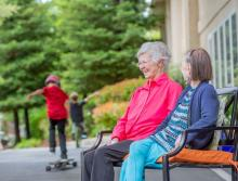 Two women resident sitting outside on a bench while two children are skating on their skateboards.