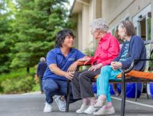 A staff member taking to two women resident sitting outside on a bench.