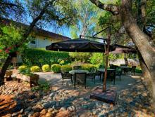 Patio with beautiful trees, plants and patio tables and umbrellas.