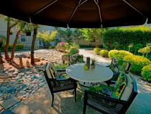 Patio table and chair under a large umbrella.