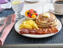 A breakfast plate with scrabbled eggs, bacon, pancakes and fresh fruit.