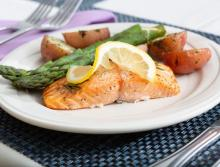 A dinner plate with salmon, asparagus, roasted red potatoes.