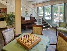 Game area with a Chess set on a table and a piano.