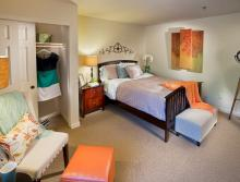 Apartment with bed, nightstand, close closet, chair and ottoman.