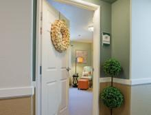 Front door and entrance into apartment with a planter outside the door.