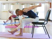 Two women sitting a chairs doing stretch exercises