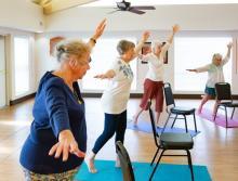 Women in an exercise class doing balancing exercises