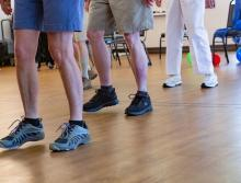 A class of residents doing step exercised to prevent falls...only their legs showing