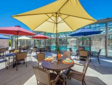 Patio tables with colorful table umbrellas next to the indoor swimming pool