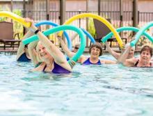 Six women in a pool doing aerobics holding foam pool noodles