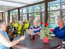 A group of residents sitting at a patio table enjoying some ice tea