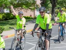 A group of residents, in their bright green shirts, riding their bikes