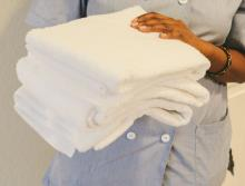 Housekeeping staff with a stack of clean white towels