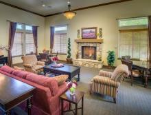 Community living room with a fireplace, couch, two comfy chairs, and a table with four chairs
