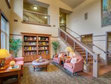 Lobby area with a couch and two chair and  book shelves with several books