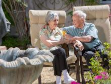 A smiling couple with their arms around each other, sitting outside next to a fountain and garden area.