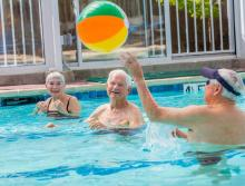 Residents in the in-door swimming pool tossing a beach ball to each other.