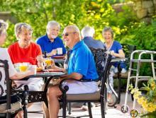 Six residents having breakfast on patio.
