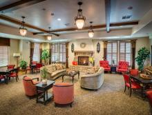Village Center's community room with couches, chairs game tables and fireplace.