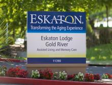 Eskaton Lodge Gold River sign with red and white flower planted below it.