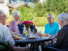 Four residents sitting around the outside patio table socializing