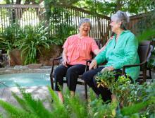 Two Eskaton Monroe Lodge women residents socializing around spa  patio area.