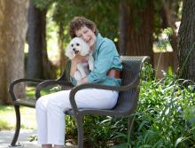 women sitting on an outside bench smiling and hugging her dog