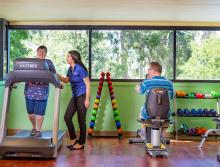 A woman on a treadmill and a man on a stationary bike in the exercise room with a staff member