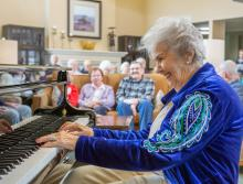 A smiling woman playing the piano for a group of residents.