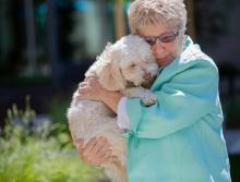 Resident holding and hugging her dog