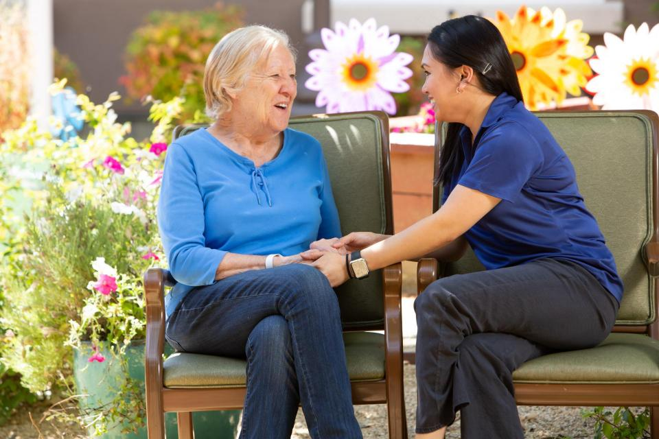 Woman resident and a staff member sitting in the garden talking an holding hands.