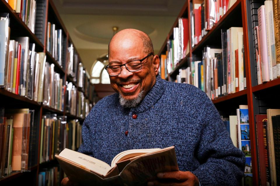 "Judge Rudolph ""Barry"" Loncke sitting in a library reading a book and smiling."