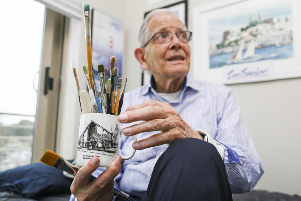 Resident Dale holding a cup full of pencils and paint brushes.
