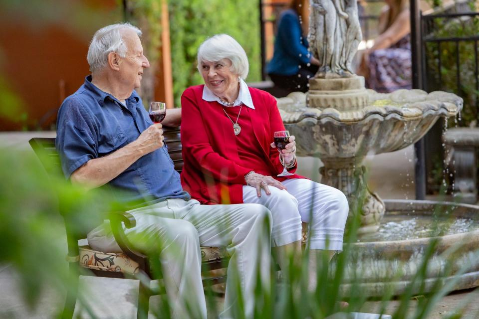 Couple sitting by water fountain enjoying a glass of red wine.