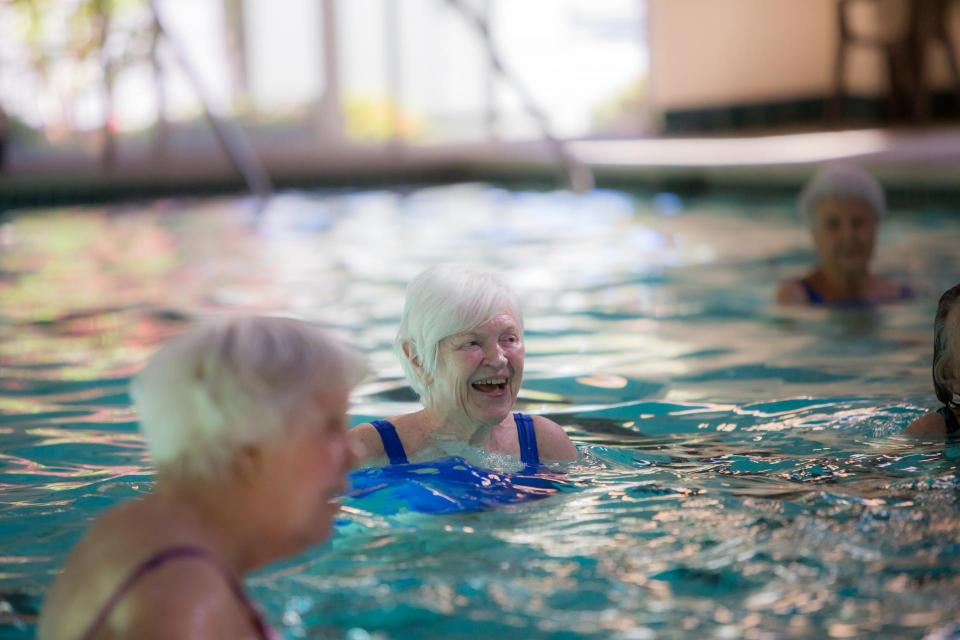 Residents enjoying a water aerobics class in the community indoor pool.